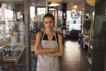 Portrait of waitress standing with arms crossed in coffee shop — Stock Photo