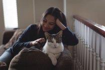 Девочка-подросток сидит с кошкой на диване в гостиной дома — стоковое фото