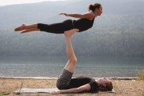 Pareja deportiva practicando acro yoga cerca de la costa del mar en un día  soleado - 17d18007df6f