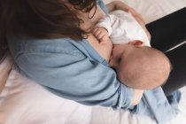 High angle view of mother sitting on bed breastfeeding her baby at home — Stock Photo