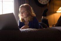 Junge Frau liegt zu Hause mit Laptop im Bett — Stockfoto