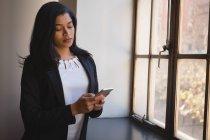 Femme d'affaires à l'aide de téléphone portable près de fenêtre au bureau — Photo de stock