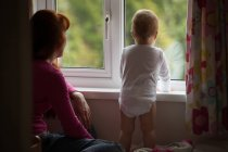 Mother with her baby girl looking through window at home — Stock Photo