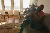 Отец помогает сыну носить одежду в гостиной дома . — стоковое фото