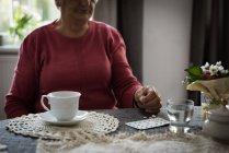 Seção intermediária de sênior mulher olhando para medicamentos na sala de estar — Fotografia de Stock