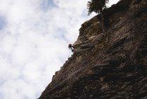 Vista a basso angolo dell'arrampicatore che sale sulla scogliera rocciosa — Foto stock