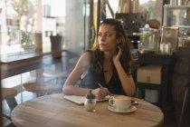 Thoughtful woman writing on diary in coffee shop — Stock Photo