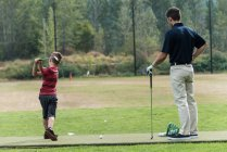 Father and son playing golf on golf course — Stock Photo