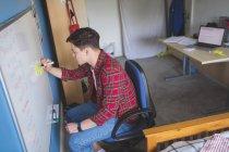 Молодой человек писать на белой доске в интерьере комнаты — стоковое фото