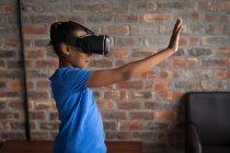 Menina pré-adolescente usando fone de ouvido realidade virtual no escritório . — Fotografia de Stock