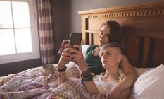 Lesbian couple taking selfie in bed at home. — Stock Photo