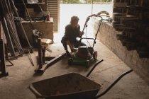 Woman repairing lawn mower in workshop — Stock Photo