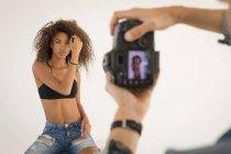 Профессиональный фотограф фотографирует модель в студии — стоковое фото