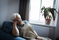 Senior mujer de relax en el sillón en la sala de estar en casa - foto de stock