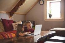 Frère à l'aide de portable sur la table à la maison — Photo de stock