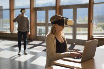 Étudiants universitaires utilisant un ordinateur portable et un casque de réalité virtuelle à table — Photo de stock