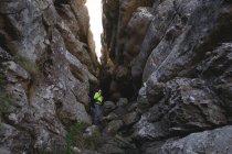 Турист, дивлячись при стоячи st вхід до печери з рюкзака — стокове фото