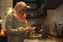 Muslim woman writing down the recipe from laptop in kitchen — Stock Photo