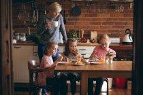 Mãe e filha tomando café da manhã na mesa na cozinha — Fotografia de Stock