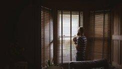Человек, стоящий у окна и пьющий кофе дома — стоковое фото