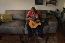 Отец и сын играют на гитаре на диване в гостиной дома . — стоковое фото