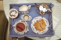 Vista aérea de bandeja con té y galletas - foto de stock