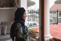 Femme musulmane réfléchie regardant par la fenêtre — Photo de stock