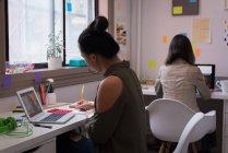 Due stilisti che lavorano sui computer portatili nello studio di design . — Foto stock
