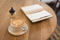 Кубок капучіно з щоденник на стіл в кафе — стокове фото