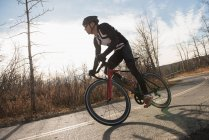 Biker riding mountain bike on road on a sunny day — Stock Photo