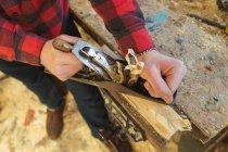 Nahaufnahme eines Tischlers mit einem Hobelwerkzeug in der Werkstatt — Stockfoto