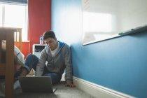 Jeune homme de travail avec ordinateur portable tout en étant assis sur le sol dans la chambre. — Photo de stock
