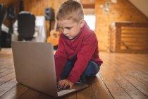 Lindo niño usando el ordenador portátil en el suelo en casa - foto de stock