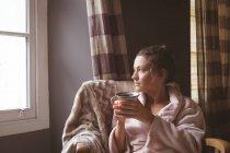 Femme réfléchie prenant un café dans la chambre et regardant par la fenêtre à la maison . — Photo de stock