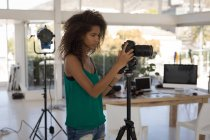 Beautiful photographer taking pictures in the studio — Stock Photo