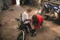 Матері, підготовка її син їздою на велосипеді в гаражі — стокове фото