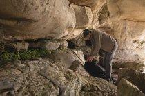 Escursionista che controlla il suo zaino nella grotta in una giornata di sole — Foto stock