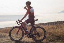 Mountain biker l'eau potable sur la campagne par une journée ensoleillée — Photo de stock