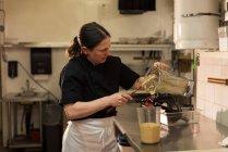 Koch Entleerung einen Boden einfügen in einen Behälter an gewerbliche Küche — Stockfoto