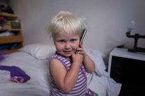 Petite fille parlant sur téléphone portable dans la chambre à coucher à la maison . — Photo de stock