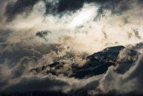 Cima de la montaña rodeada de nubes en la noche - foto de stock