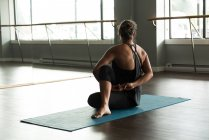 Femme pratiquant l'exercice d'étirement dans le studio de remise en forme. — Photo de stock