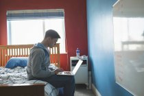Young man using laptop while sitting on bed in bedroom, side view. — Stock Photo