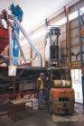 Homme levage sac de grains avec chariot élévateur à fourche dans l'usine — Photo de stock