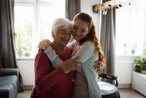 Lächelnde Großmutter und Enkelin umarmen sich im Wohnzimmer — Stockfoto