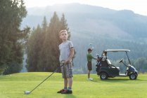 Thoughtful boy standing with golf club in the course — Stock Photo