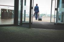 Vue arrière d'homme d'affaires à pied de l'hôtel avec bagages — Photo de stock