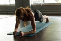 Young man with long red hair doing plank exercise in fitness studio. — Stock Photo