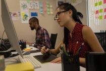 Progettista grafico femminile utilizzando la tavoletta grafica allo scrittorio in ufficio — Foto stock