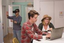 Керівники обговорювати над ноутбук в творчих office — стокове фото